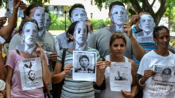 Members of the Ladies in White Cuban dissident group pose wearing masks depicting US President Barack Obama and holding pictures of imprisoned dissidents as they protest against the reopening of the US embassy, on August 9, 2015.