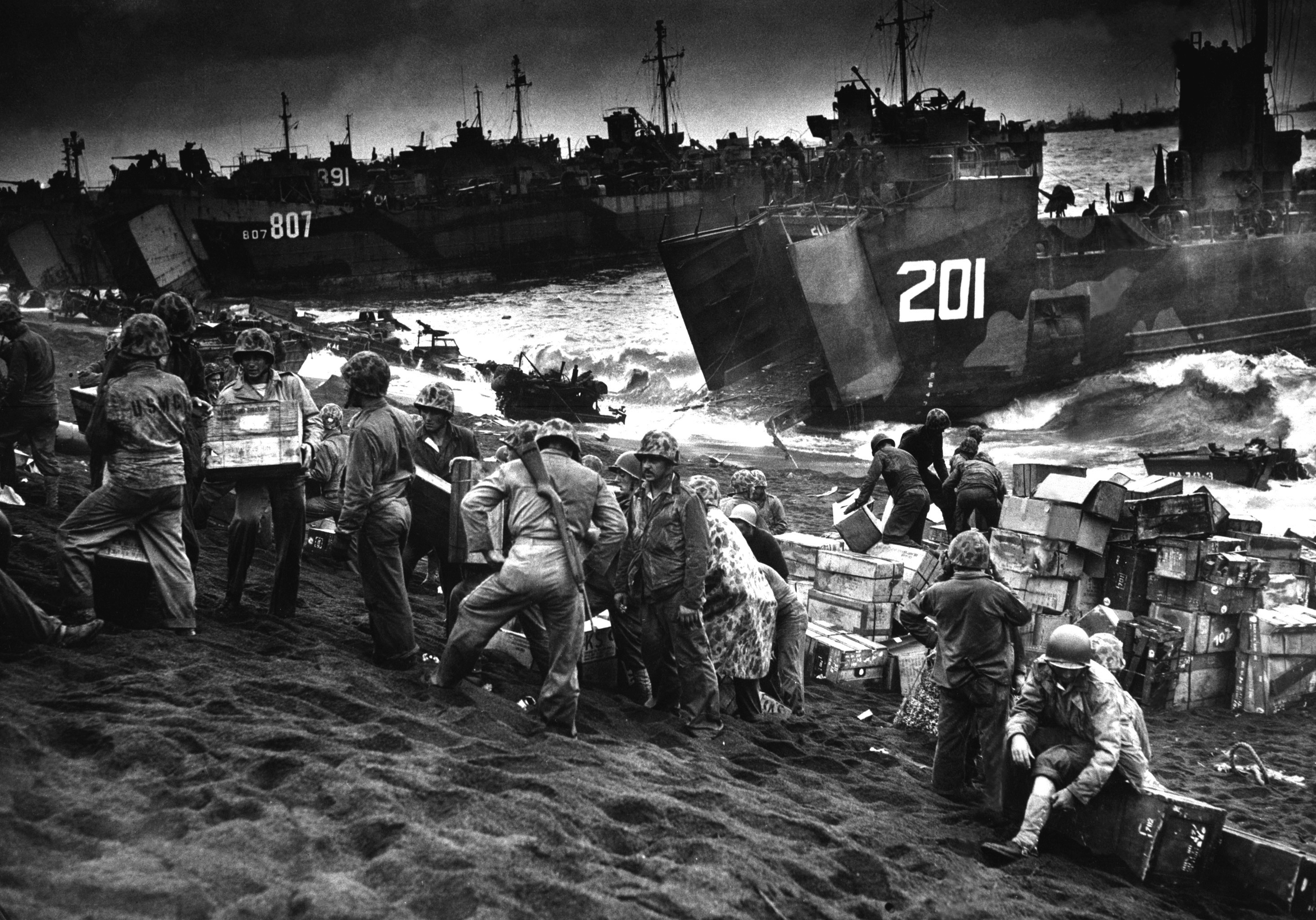 Out of the gaping mouths of Coast Guard and Navy Landing Craft, rose the great flow of invasion supplies to the blackened sands of Iwo Jima, a few hours after the Marines had wrested their foothold on the vital island.